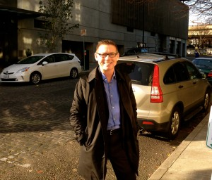Tom Krattenmaker stands on the street outside the Pearl District condo where he lives with his wife.